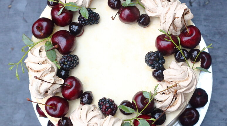 Banana rum cake decorated with fresh cherries and meringues