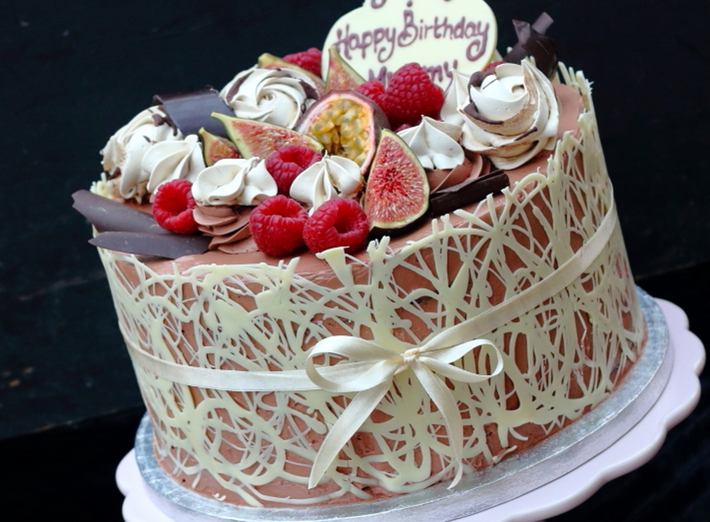 Chocolate fudge cake covered with white chocolate collar and fresh fruit on top