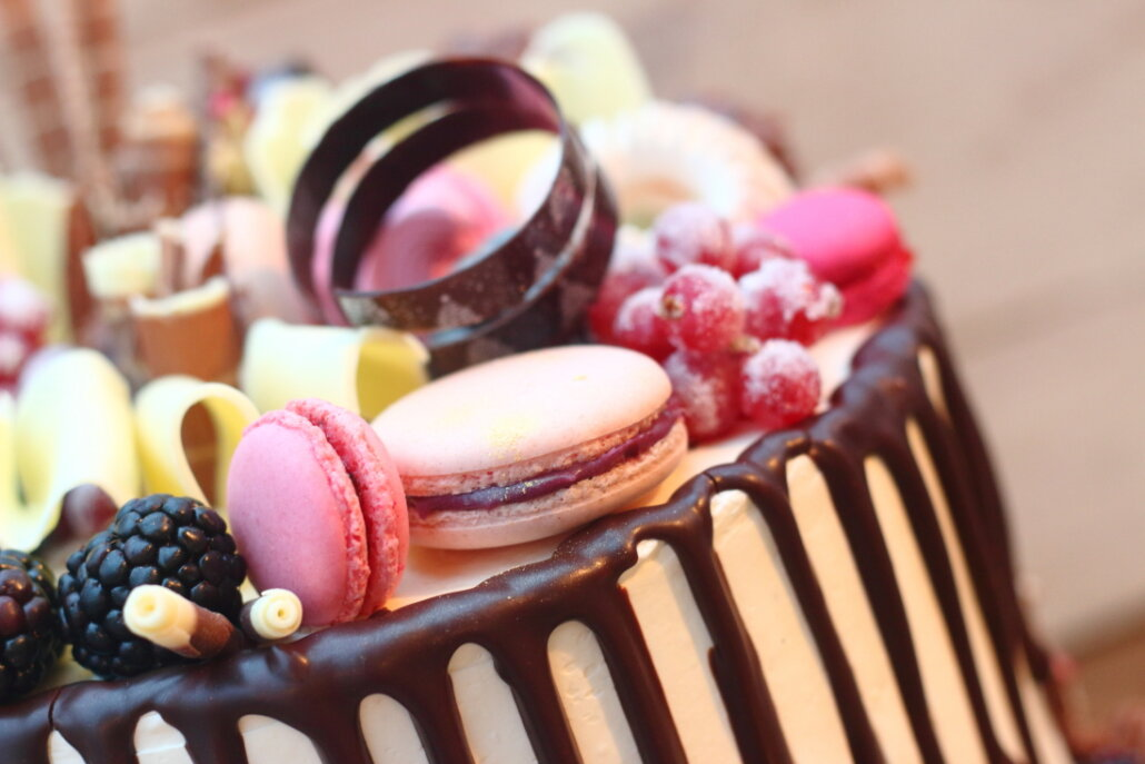Close-up of macarons and chocolate curls on an elegant chocolate cake