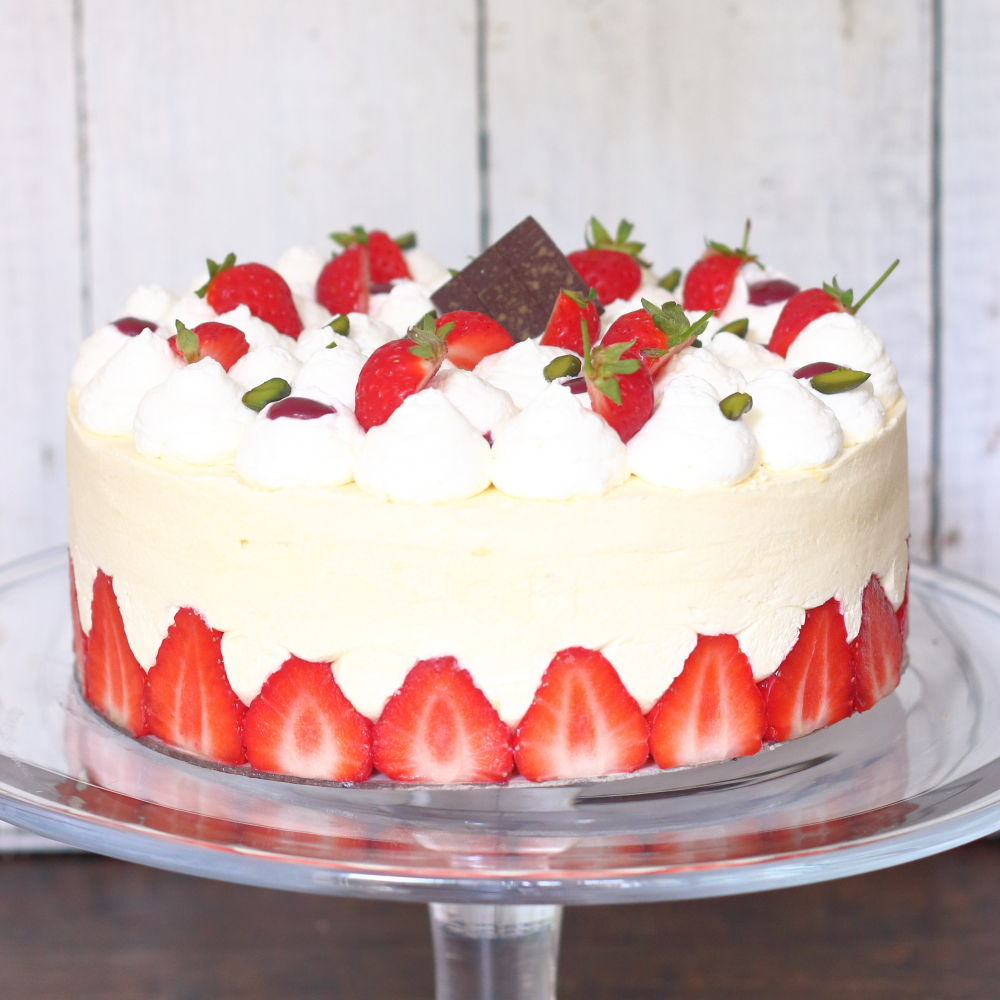 Strawberry cream cake on a cake stamd by lovingly baked by anthea