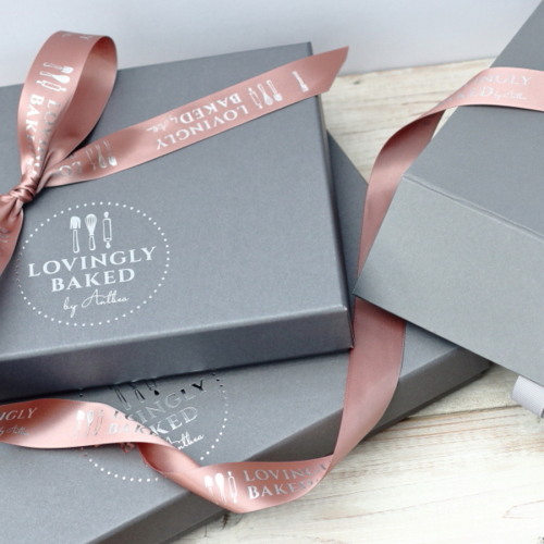 Grey gift boxes tied with pink ribbon with Lovingly Baked by Anthea logo to order online