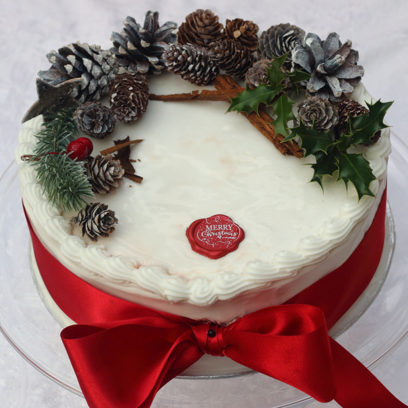 Traditional Christmas cake with royal icing, red ribbon and pine cones, by Lovingly Baked by Anthea in Grayshott Surrey